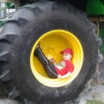 child sits in large tractor wheel