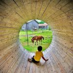 child sits in large wooden tunnel